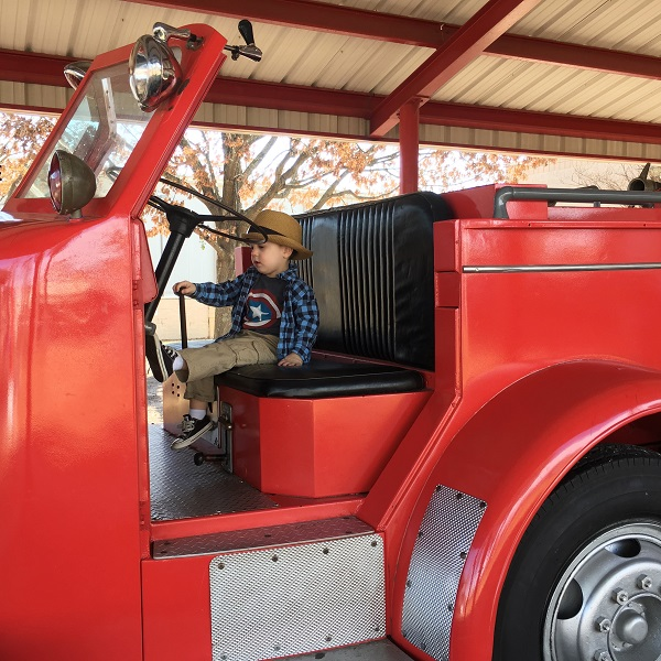 Gavin on the fire truck at a playground | rainerlife.com